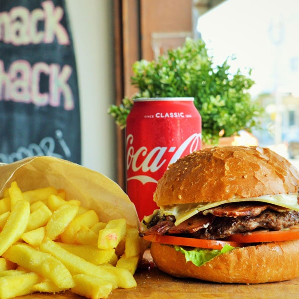 Surf Club Burger with House-made beef patty, bacon, cheese, tomato, lettuce & Shack Aioli. Chips and a can of coke